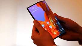 A member of Huawei staff shows the new Huawei Mate X device during a pre-briefing display ahead of t