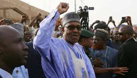 Nigerian President Muhammadu Buhari gestures as he arrives to cast a vote in Nigeria's presidential
