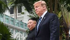 US President Donald Trump (R) walks with North Korea's leader Kim Jong Un during a break in talks at