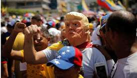 A man wearing a mask of Trump gestures during a rally against Venezuelan President Nicolas Maduro's