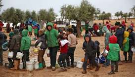 Syrian children queue to receive food distributed by humanitarian aid workers at a makeshift camp fo