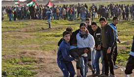 Palestinian demonstrators evacuate a wounded comrade during a demonstration near the fence along the