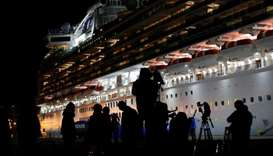 Reporters are silhouetted in front of the cruise ship Diamond Princess