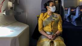 A flight attendant wearing a protective face mask is pictured during a flight from Sydney to Bangkok