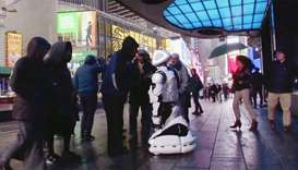 Passers-by in Times Square interact with a Promobot robot that informs the public about the symptoms