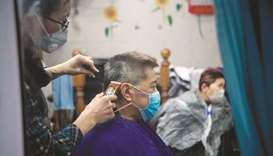 A man wearing a protective face mask has his hair cut by a barber in Shanghai yesterday.