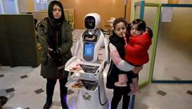Afghan girls pose for a photo with a waitress robot (Timea) at the Times Fast Food restaurant in Kab