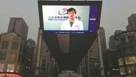 A news item about the COVID-19 coronavirus plays on a giant screen outside a shopping mall in Beijin