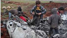 Syrians inspect the wreckage of a military helicopter belonging to government forces after it was sh