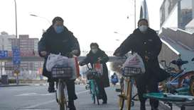 Women wearing face masks ride shared bicycles in Beijing