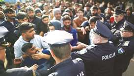 Migrants scuffle with police as they try to block a road in front of the Miral refugee camp in Velik