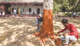Labourers give finishing touches to a tree in front of the 'Hriday Kunj', the house where Mahatma Ga