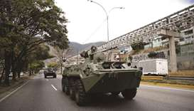 A soldier is seen on an armoured vehicle driven along a highway during a military exercises in Carac