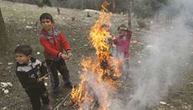 Internally displaced children warm themselves around a fire in Qatmah village, West of Azaz, yesterd