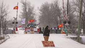 A man with a sign stands near the site of a rail stoppage on Tyendinaga Mohawk Territory, as part of