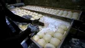 A worker prepares bread dough before baking in a traditional oven at a bakery in Khartoum