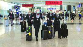 Flight attendants wear protective masks as they walk through the arrivals hall at the Hong Kong Inte