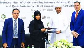 Mohamed Essa al-Boainain and Professor Mariam Ali al-Maadeed shaking hands after signing the MoU in
