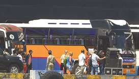 Passengers from the Westerdam cruise ship prepare to board a bus after disembarking from the ship in