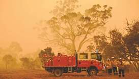 Firefighters protect a property from bushfires burning near the town of Bumbalong south of Canberra