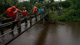 Rescue workers walk past a bridge as they search for students who were missing after a tidal surge s