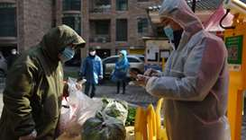 A resident collects vegetables purchased through group orders at the entrance of a residential compo