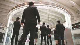 Visitors watch share prices at the Tokyo Stock Exchange in Japan. The Nikkei 225 closed down 0.4% to
