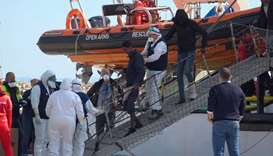 Medical officials wearing protective suits assist a migrant disembarking from 'Open Arms' rescue shi
