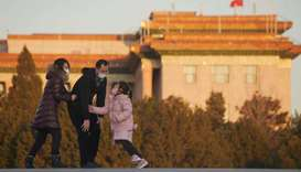 Parents wearing face masks play with their daughter with the Great Hall of the People seen in the ba
