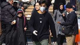 A young Iranian man wearing a protective mask, walks in a busy street in the capital Tehran
