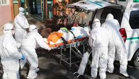 Medical workers wearing protective gear transfer a suspected coronavirus patient (C) to another hosp