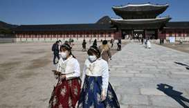 People in traditional Korean hanbok dresses wear face masks as they visit Gyeongbokgung palace in Se