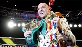 Tyson Fury poses with his belts during a press conference after the fight