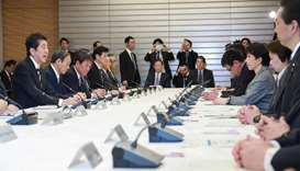 Japan's Prime Minister Shinzo Abe (L) attends a meeting at the new COVID-19 coronavirus infectious d