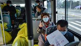 People who have recovered from the COVID-19 coronavirus infection leaving a hospital by bus in Wuhan