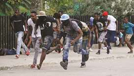 Protesters run for cover during a shooting in Champ de Mars, Port-au-Prince, Haiti.