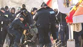Police officers make an arrest during a raid on a Tyendinaga Mohawk Territory camp next to a railway