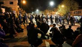 Demonstrators sit in front of riot police at the port of Mytilene as they protest against the cconst