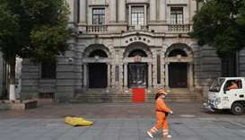A sanitation worker wearing a face mask walks past a branch of Industrial and Commercial Bank of Chi