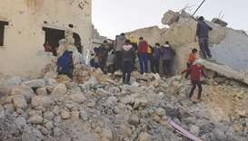 Residents and rescuers search for victims in the rubble of a building following pro-regime force air