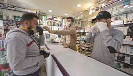 An Iraqi man checks a protective mask at a pharmacy yesterday, in the holy city of Najaf.