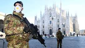 Military officers wearing face masks stand outside Duomo cathedral, closed by authorities due to a c