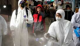 A man reacts as employees from a disinfection service company sanitize a traditional market in Seoul