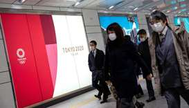 People wearing protective face masks, following an outbreak of the coronavirus, walk past an adverti