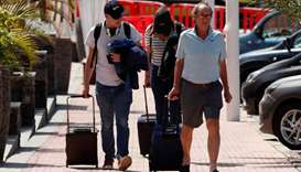 Tourists leave by foot the H10 Costa Adeje Palace hotel, which was placed on lockdown after four cas