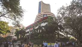 People walk by the Bombay Stock Exchange building in Mumbai. The Sensex closed down 3.64% or 1,448.3
