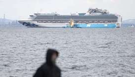 A member of the media (in foreground) looks out toward the Diamond Princess cruise ship (in backgrou