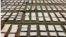 Workers set up beds at an exhibition centre that was converted into a hospital in Wuhan in China's c