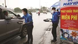 Employees of Garment 10 company provide free masks on a road in Hanoi yesterday.