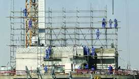 Labourers install scaffolding at a construction site in Doha